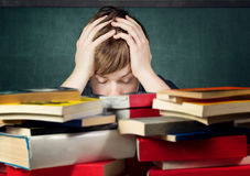Overstrained. Student overhelmed with his books Stock Photography