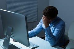 Overstressed affärsmanbenägenhet på datorskrivbordet Royaltyfri Bild