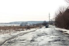 Overstroming van weg toe te schrijven aan sneeuw die en het toenemen van waterspiegel smelten Het incident van de de lentenoodsit stock foto's