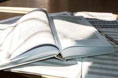 Overstroomd met licht: open boek, bladmuziek en muzieknotitieboekje Stock Afbeelding