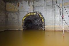 Overstroomd om de ondergrondse tunnel van het drainageriool met vuil rioleringswater die aan collector stromen stock foto's