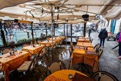Overstroomde restaurantlijst en stoelen op kanaalweg op Grand Canal, Venetië, Italië royalty-vrije stock foto