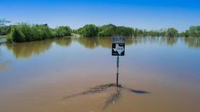 Overstroomde Rijweg van Texas en een straatteken onder water Stock Foto's