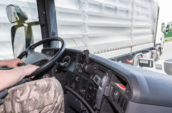 Overtaking of trucks on the road. View from the truck cab for the driver who holds the steering wheel. The truck is just overtaken by another truck. All Royalty Free Stock Photo