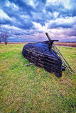 Overthrown fisherman boat on the lake shore at stormy weather Stock Photography