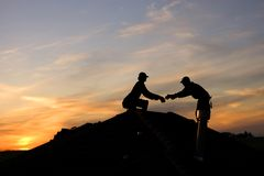 Overtime. Two roofers working late on a roof top royalty free stock photography