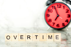 Overtime clock with text on marble Royalty Free Stock Photos