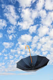 Overturn Black Umbrella flies in cloudy sky.Mary Poppins Umbrella. Royalty Free Stock Photography