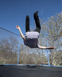 Overturn on trampoline. Child doing an overturn on a trampoline outdoors Royalty Free Stock Photo