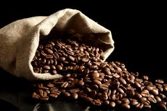 Overturned bag full of coffee beans on black Royalty Free Stock Photo