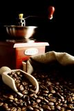 Overturned bag full of coffee beans on black with spatula,mill Royalty Free Stock Photos