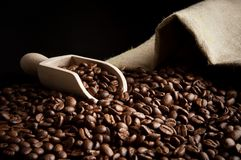 Overturned bag full of coffee beans on black with spatula Stock Images