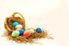 Overturned basket with coloured Easter eggs. Overturned basket with ten coloured Easter eggs with straw with copy space Royalty Free Stock Photos