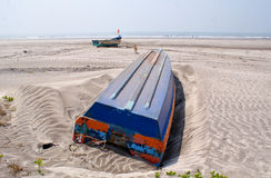 An overturned blue coloured boat in a beach in Konkan. An overturned boat abandoned in a beach in Konkan, along with another boat at a distance and a stray dog Royalty Free Stock Image