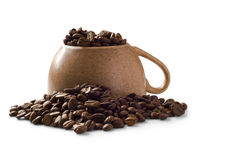 Overturned brown cup with coffee beans over it. Isolated on white background with shadow Royalty Free Stock Photography