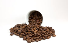 Overturned cup with coffee beans Royalty Free Stock Photos