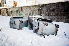Overturned garbage containers during strong and snowy winter Stock Photos