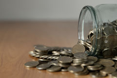 Overturned glass jar full of coins, money box Stock Photos