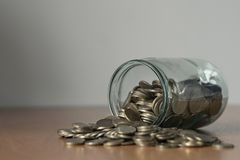 Overturned glass jar full of coins, money box Royalty Free Stock Photos