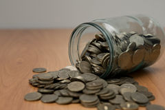 Overturned glass jar full of coins, money box Royalty Free Stock Images