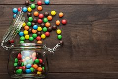 Overturned glass jar full of colorful sweets Royalty Free Stock Photography