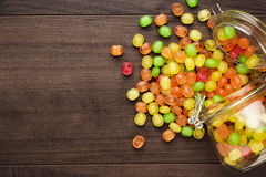 Overturned glass jar full of colorful sweets Royalty Free Stock Images