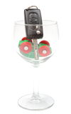 Overturned model vehicle and car key in glass of wine. White background Stock Photos