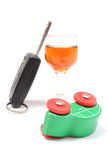 Overturned model vehicle, glass of wine and car key. White background Royalty Free Stock Photos