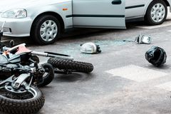 Motorcycle after collision with car. Overturned motorcycle and helmet on the road after a collision with a car royalty free stock photo