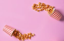 Overturned paper buckets with scattered caramel popcorn on color background