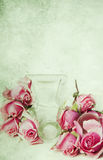Overturned perfume bottle and tea roses Stock Images