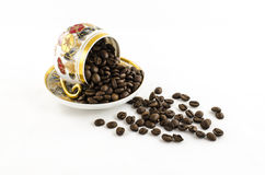 Overturned porcelain coffee cup with coffee beans isolated on white Stock Photo