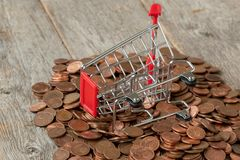 Overturned shopping cart with coins royalty free stock photos