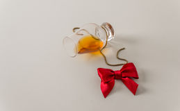 Overturned single malt whiskey glass, on white, with gold chain Royalty Free Stock Photo