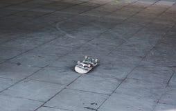 Overturned upside down alone skateboard on playground Stock Photo