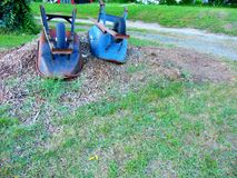 Overturned wheelbarrows. On mound of mulch royalty free stock photo
