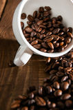 Overturned white cup with coffee beans Royalty Free Stock Image