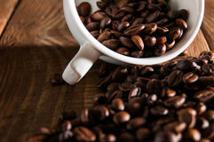 Overturned white cup with coffee beans Stock Photos