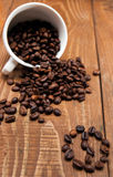 Overturned white cup with coffee beans Stock Photography