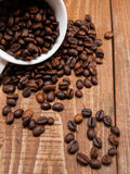 Overturned white cup with coffee beans Royalty Free Stock Photo