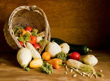 Overturned wicker basket full with various fresh vegetables on wooden background. Overturned wicker basket full with various fresh vegetables on the table Royalty Free Stock Images