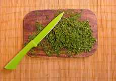 Overview of chopped dill on a wooden board with a colored knife. A view from above on chopped dill on a wooden board with a colored knife Royalty Free Stock Image