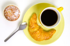 Overview of a coffee mug with croissant and a cupcake. A view from above on a mug of black coffee, an organic croissant and a cupcake Royalty Free Stock Photography