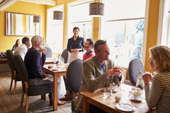 Overview of customers and a waitress in restaurant interior Royalty Free Stock Image