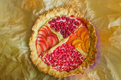 Overview of a freshly made fruit pie in baking paper. A freshly made colorful fruit and berry pie with it's baking paper still around it Stock Images