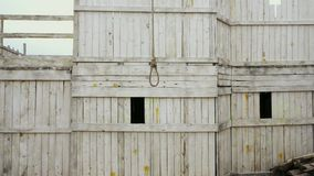 Overview hangman gallow with loop durable rope for suicide wooden background 4K.