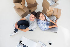 Overview of a happy couple sitting back to back. In their new house Royalty Free Stock Photos