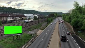 Overview of highway and green screen billboard in Steel town. A high-angle overview of a highway and green screen billboard near old factories along the Ohio stock video footage