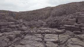 Overview of immense windswept rocky terraces, gray ancient geological formations