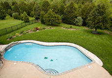 Overview of luxury pool. View of luxury pool and deck with surrounding landscaped garden with flowers and trees stock images